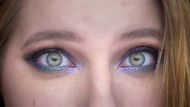 Closeup hajtás fiatal szép női arc szemmel néztem kamera meglepett arckifejezés gyönyörű smink alkalmazott