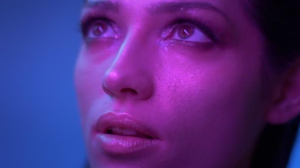 Úžasný módní model s třpytivě očními stíny v purpurově neonové světelné reflektory se zasněně dívá nahoru.