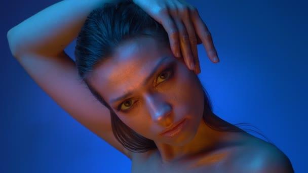 Zářící model s lesklým make-upem, který stojí v modrých neonových světlech a dává ruku přes hlavu a dívá se do kamery.