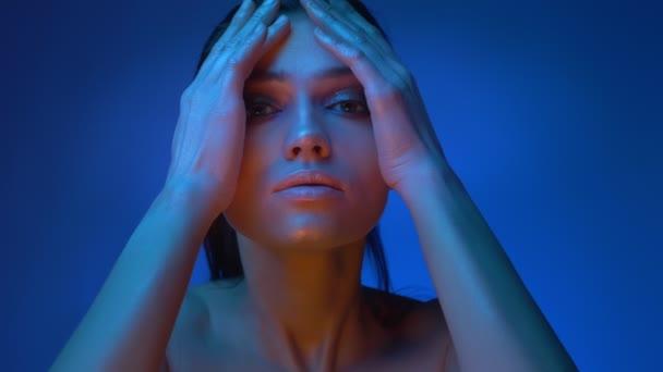 Fényes futurisztikus divat modell hideg kék neon fények simogatva az arcát és a haját lassan néz nyugodtan a kamera.