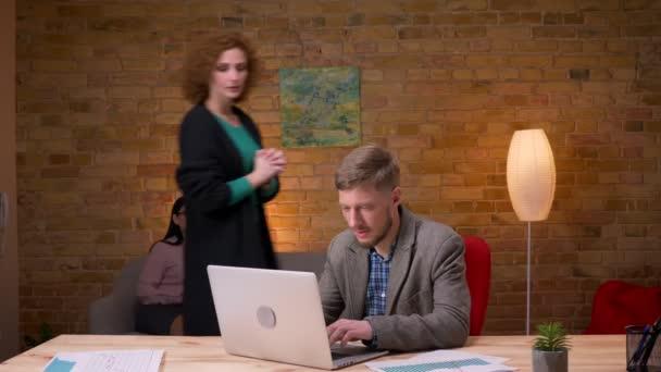 Nahaufnahme eines jungen Geschäftsmannes, der drinnen im Büro am Laptop arbeitet. Mitarbeiterin erzählt ihm schlechte Nachrichten und macht Arbeitgeber wütend