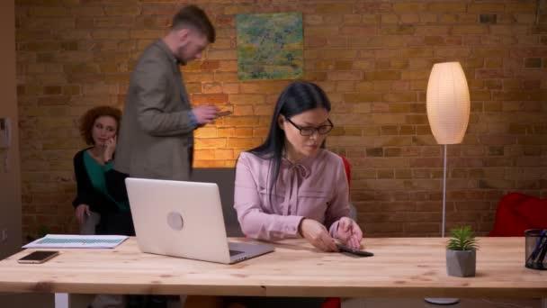 Closeup hajtás felnőtt ázsiai üzletasszony dolgozik a laptop kap értesítést a telefon mosolygó és megosztása jó hír, boldog kollégák. Nő alkalmazottja segítségével a mobiltelefon a