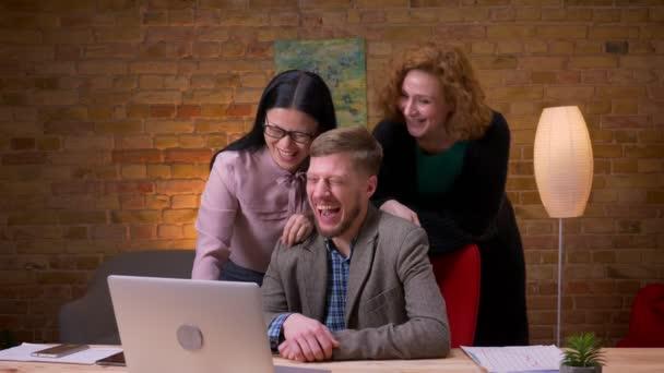 Closeup lő három barátságos kollégák, amelyek a videohívás a laptop nevetve, és a szórakozás beltérben a telefon