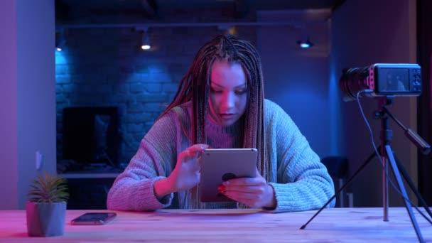 Closeup, mladý atraktivní ženský blogger s dredy, s úsměvem na tabletu, usmívá se vesele, žije s neonové pozadí uvnitř