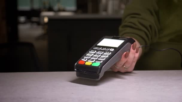 Close-up shot of person using terminal and credit card performs contactless payment and prints the check.