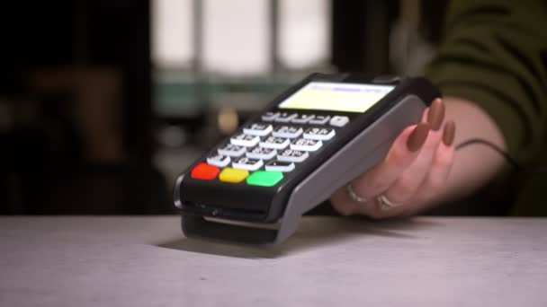 Close-up shot of person applies credit card to terminal performing contactless payment.