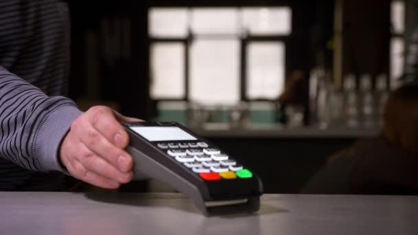 Zavodka ženy vloží kreditní kartu do terminálu vykonávající platbu za odměnu.