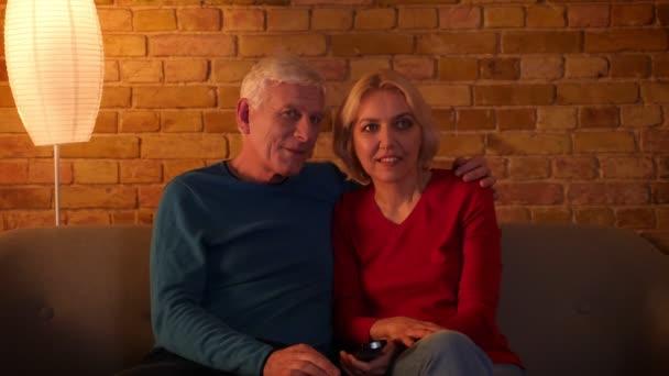 Closeup lő a magas rangú boldog pár néz egy TV film mosolygó vidáman ül a kanapén beltérben egy hangulatos lakásban..