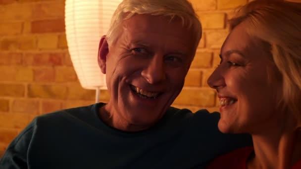 V útulném bytě se střílejí ze starých šťastných pár, jak se usmívá televize.