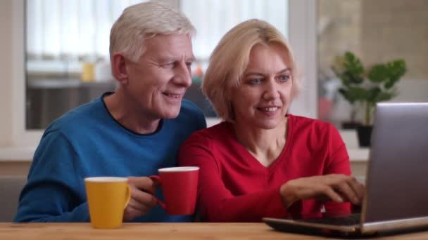 Closeup střílejí ze starších šťastných pár sítí na přenosném počítači na stole a popíjet čaj v útulném bytě