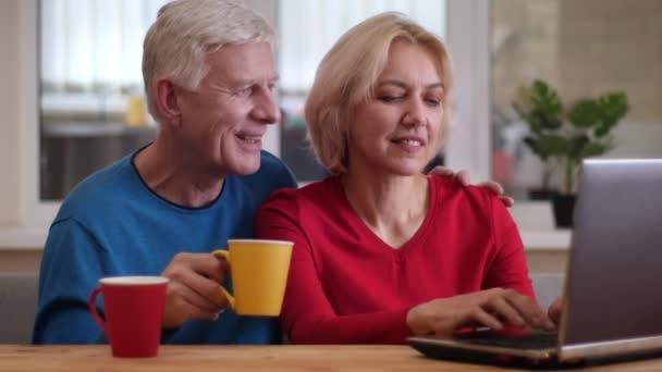 Closeup Střílej ze starších šťastných pár sítí na přenosném počítači na stole a popíjet kávu uvnitř útulného bytu