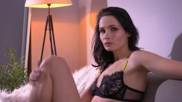 Portrét něžného bruneta modelu v černém prádle opřený o kolena a flirtování s fotoaparátem v domácí atmosféře.