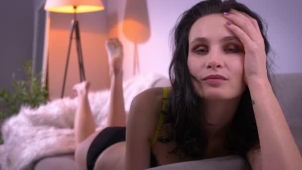 Voluptuous Brünette Modell in schwarzen Dessous entspannen auf Sofa Fixierung Haare und flirten mit der Kamera in häuslicher Atmosphäre.