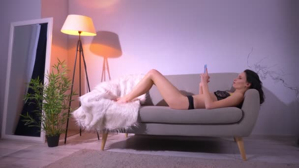 Voluptuous brunette model in black lingerie lying on sofa and working with smartphone in home atmosphere.