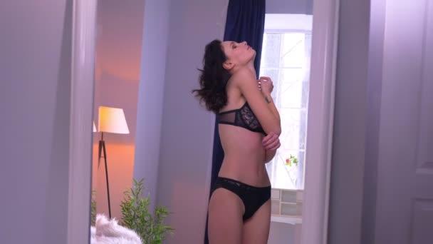 Portrét něžného a sexy bruneta v černém prádle, pozorování v zrcadle s obdivem domácí atmosféry.