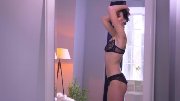 Portrét hezkou a sexy brunetového modelu v černém prádle, který se točí kolem sebe v zrcadle doma.