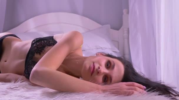 Porträt eines sexy brünetten Models in schwarzer Dessous, das auf einem Himmelbett liegt und sich zärtlich in häuslicher Atmosphäre wälzt.