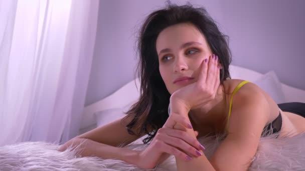 Blízkou ránu sexy brunetky v černém prádle na ruce, která se příjemně dívá do kamery doma.
