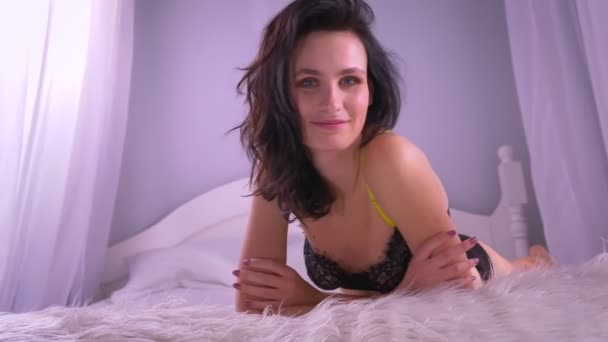 Blízkou ránu sexy bruneta v černém prádle upravuje vlasy, které se zasněně dívají do kamery doma.