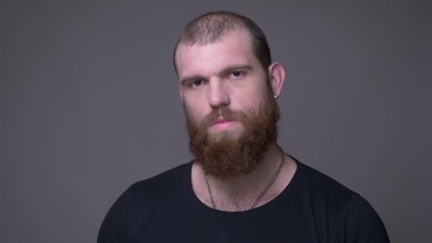 Střevný šat dospělého muže ze svalstva s plnovousem a s bradkou na kameru s agresí s pozadím izolovaným na šedé