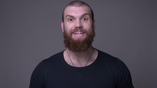 Střevný zastřelený krásný svalnatý muž s plnovousem, vzrušený a překvapený pohledem na fotoaparát s pozadím izolovaným na šedé