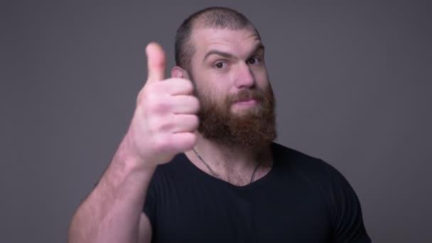 Střelili se s plnovousem, hezký svalnatý muž s bradkou, s úsměvem na palec a pohledem na kameru s pozadím na šedé