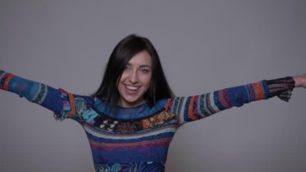Closeup portrét dospělé kavkazské bruneté ženy otáčející se s rozvlanýma vlasama usmívaje se s radostí pohledem na fotoaparát s pozadím izolovaným na šedé