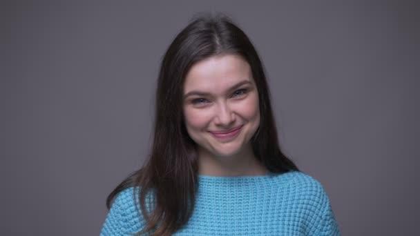 Šneka Mladá hezká brunetka usmívající se s plachtou, která hledí na kameru s pozadím izolovaným na šedém