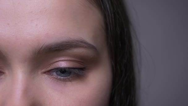 Closeup fél-arc lő a fiatal, vonzó női arc, kék csillogó szemmel nézett kamera