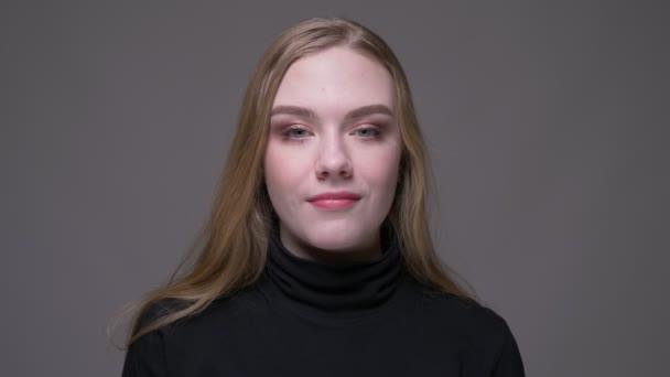 Closeup portré fiatal vonzó barna női mosolygó boldogan nézi kamera háttérrel izolált szürke