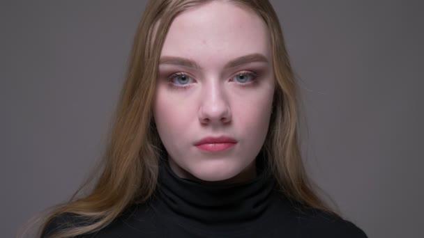 Closeup portrét mladé atraktivní bruneté ženské tváře, která se dívá na fotoaparát s pozadím izolovaným na šedé