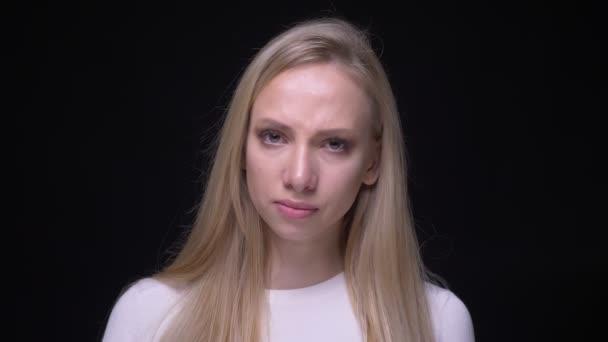 Closeup portrét mladé, hezké ženské ženy, která je smutná a deprimovaná pláče a dívá se na kameru s pozadím izolovaným na černém