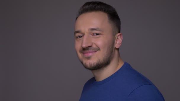 Zastřelte mladého pohledného bělošského muže, jak se otáčí a dívá se na kameru a usmívá se na pozadí izolovaně na šedé