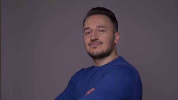 Střelili mladého pohledného kavkazského muže s důvěrou s rukama zkříženýma na prsou a dívali se na kameru s pozadím izolovaným na šedé