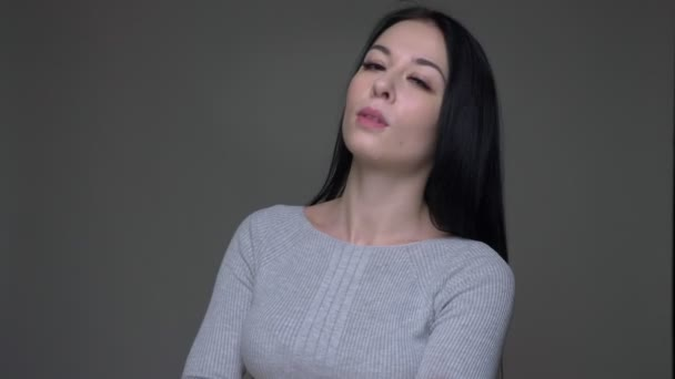 Closeup shoot of young pretty caucasian female posing with her arms crossed over chest and looking straight at camera with background isolated on gray