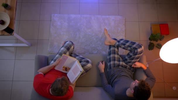 Top Shot barátai hálóruha kapcsolási TV-műsorok távirányítóval és olvasott könyv a nappaliban.