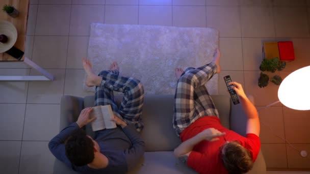 Nejlepší záběr přátel v náměsíčnici sleduje film s dálkovým ovládači a pozorně čte knihu v obývacím pokoji.