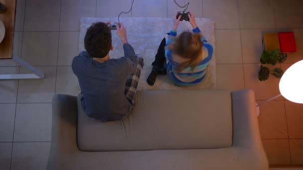 Tető szemcsésedik-ból fiatal pár-ban hálóruhák játék videogame-val joystickok ülő-ra dívány és emelet-ban nappali.