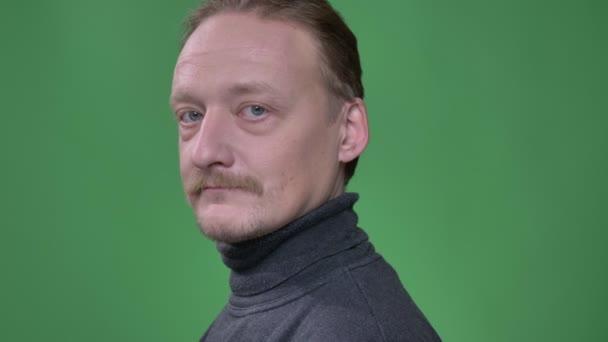 Portrét muže středního věku s vousy se mění na kameru a šťastně se do něj usměje s překvapením na zeleném pozadí.