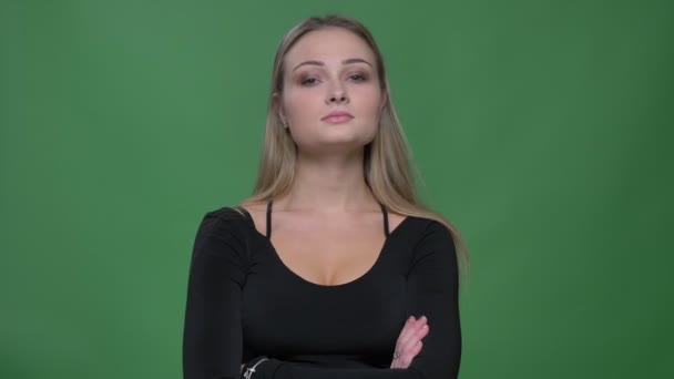 Portrait of young businesswoman in black blouse watching into camera interrogatively at green background.