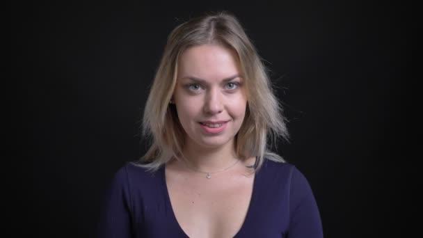 Šťastná blondýnka středního věku v modrých blůzovcích se usmívá do kamery na černém pozadí.