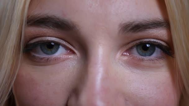 Closeup lő a fiatal csinos szőke kaukázusi női arc, kék szemmel keres egyenesen a kamera