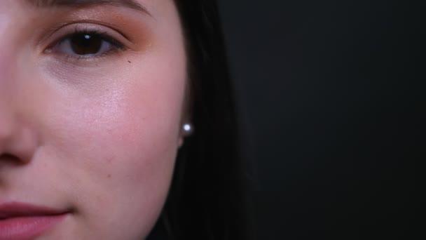 Closeup napůl tvář portrét mladé atraktivní Brunetky s hezkým make-upem, který vypadá přímo na kameru s pozadím na černém