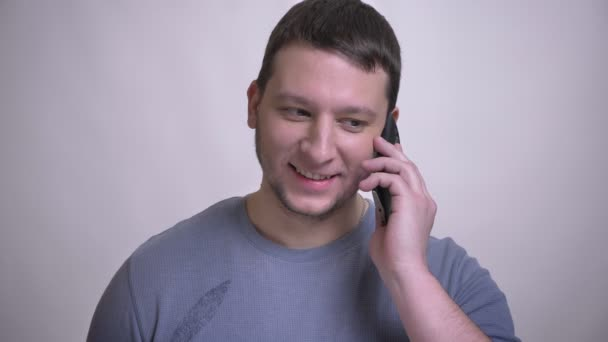 Closeup portrait of adult attractive caucasian man having a phone call smiling happily with background isolated on white