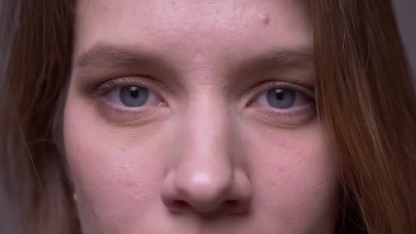 Nahaufnahme eines hübschen jungen Mädchens, das in die Kamera schaut, bricht in ein glückliches Lächeln aus..