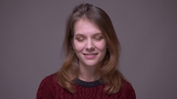 Pretty young female student watching smilingly into camera being shy on gray background.
