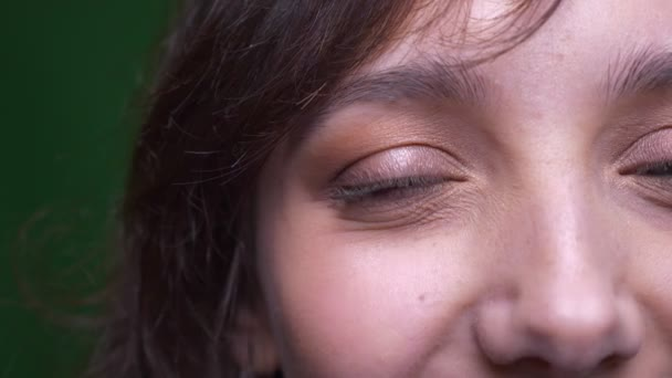 Közelkép fél arcképe fiatal barna nő diák figyelte mosolygó a kamera zöld háttér.