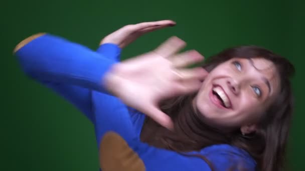 Young brunette female student dancing strangely and actively to the music on green background.