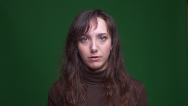 Young brunette female student shows facepalm gesture being irritated and disenchanted on green background.