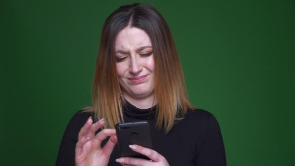junge Geschäftsfrau mit kastanienbraunem Haar schaut ratlos und verwirrt in ihr Handy auf grünem Hintergrund.